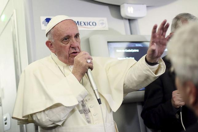 Pope Francis gestures during a meeting with the media onboard the papal plane while en route to Rome.   REUTERS/Alessandro Di Meo/Pool
