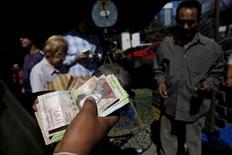 Un hombre cuenta bolívares en una verdulería en una calle de Caracas. 16 de enero de 2016. La economía venezolana se contrajo un 5,7 por ciento en el 2015, dijo el jueves el Banco Central, y reportó que la inflación se aceleró un 180,9 por ciento en el ejercicio. REUTERS/Carlos Garcia Rawlins