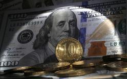 Стодолларовая банкнота и 10-рублевые монеты.  Рубль начал биржевые торги пятницы незначительными изменениями перед длинными российскими праздниками, сразу после которых будет пик налоговых выплат. REUTERS/Alexander Demianchuk (RUSSIA - Tags: BUSINESS)