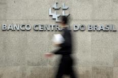Un hombre camina al logo del Banco Central de Brasil, en Brasilia. 15 de enero de 2014. El Banco Central de Brasil no está considerando aplicar recortes a las tasas de interés como parte de sus planes para que la inflación vuelva al 4,5 por ciento, en el centro del rango de una meta oficial para el 2017, dijo Almatir Lopes, director de la entidad. REUTERS/Ueslei Marcelino
