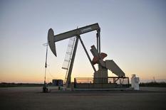 Una unidad de bombeo de crudo operada por la firma Devon Energy en los alrededores de Guthrie, EEUU, sep 15, 2015. Los precios del petróleo caían con fuerza el viernes, debido a que las conversaciones entre algunos productores para congelar el bombeo eran contrarrestadas por las preocupaciones por un exceso de oferta en el mercado tras un alza récord en los inventarios de crudo en Estados Unidos.     REUTERS/Nick Oxford