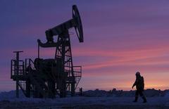 Рабочий проходит мимо нефтедобывающей установки на месторождении в районе селения Николо-Березовка к северо-западу от Уфы в России 28 января 2015 года. Переизбыток нефти на глобальном рынке составляет около 1,8 миллионов баррелей в сутки, но может сократиться вдвое, если соглашение с саудитами и другими добытчиками воплотится в жизнь, сказал в пятницу чиновник российского Минэнерго.  REUTERS/Sergei Karpukhin/Files