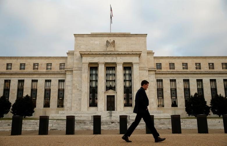 A man walks past the Federal Reserve in Washington, December 16, 2015. REUTERS/Kevin Lamarque