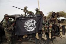 Nigerien soldiers hold up a Boko Haram flag that they had seized in the recently retaken town of Damasak, Nigeria, March 18, 2015.  REUTERS/Emmanuel Braun