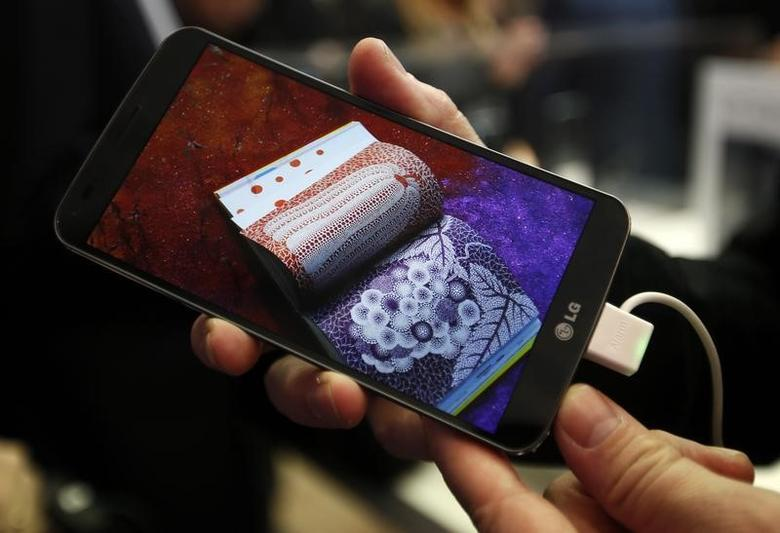 A model holds a curved G Flex smartphone by LG Electronics during the Mobile World Congress (MWC) in Barcelona February 24, 2014. REUTERS/Gustau Nacarino