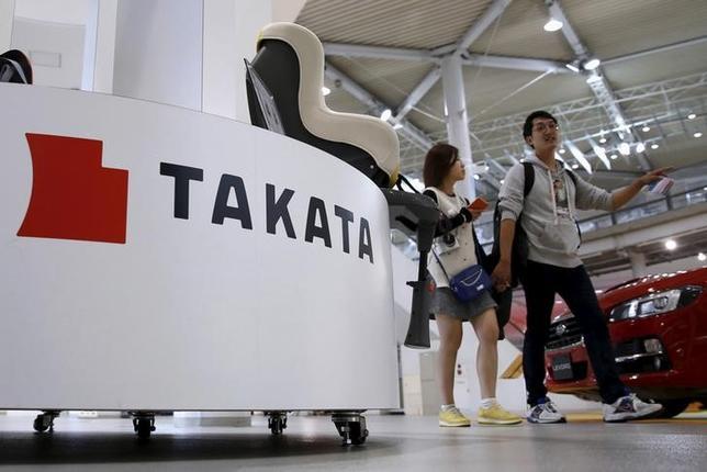 Visitors walk behind a logo of Takata Corp on its display at a showroom for vehicles in Tokyo, Japan, November 6, 2015. REUTERS/Toru Hanai/Files