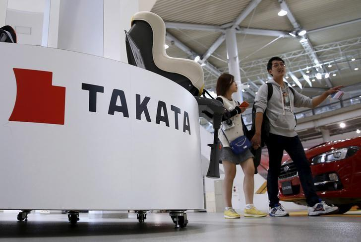 Visitors walk behind a logo of Takata Corp on its display at a showroom for vehicles in Tokyo, Japan, November 6, 2015. REUTERS/Toru Hanai/Files