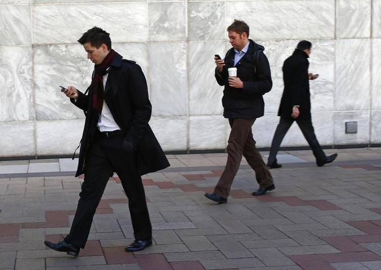 Workers look at their phones while walking at the Canary Wharf business district in London in this February 26, 2014 file photo. REUTERS/Eddie Keogh