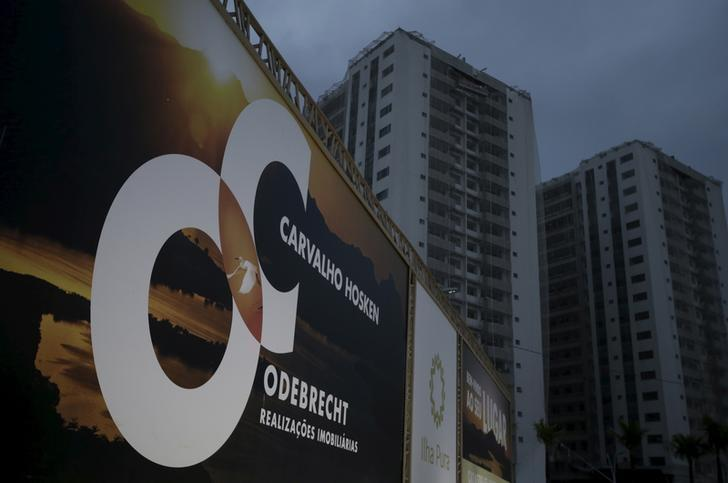 A banner of Odebrecht SA is pictured in front of buildings under construction at the Rio 2016 Olympic Games athletes village in Rio de Janeiro, Brazil July 21, 2015.  REUTERS/Ricardo Moraes