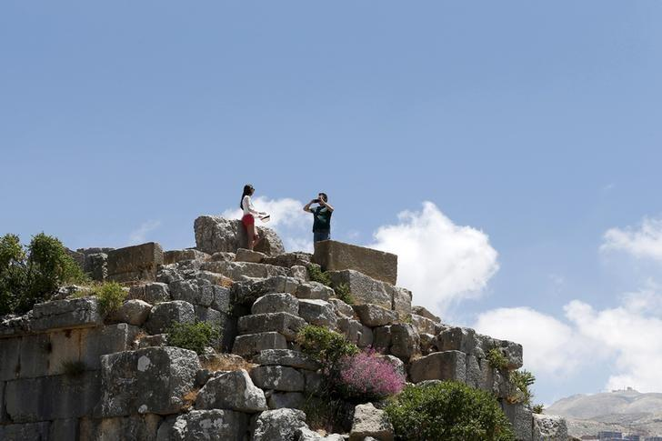 Tourists take pictures on Greek ruins in Faqra, Mount Lebanon, July 5, 2015. REUTERS/Jamal Saidi