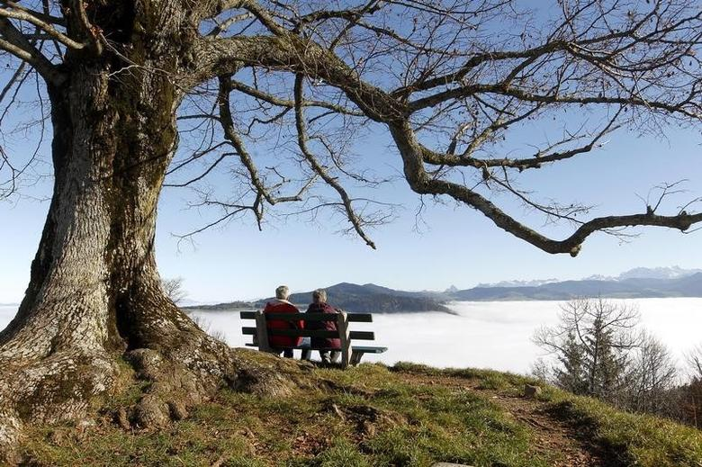 An elderly couple sits on a bench on the peak of Mount Hochwacht (988 metres/3241 ft) as high fog covers the landscape around the Swiss town of Zug in this file photo dated November 20, 2012. Reuters/Arnd Wiegmann