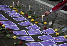 A supporter lights candles surrounding photos of murdered women outside the Missing Women's Commission of Inquiry being made public in Vancouver, British Columbia December 17, 2012. The 1,448-page report examines the mishandling of the Robert Pickton serial killer case by the Vancouver Police Department (VPD).  REUTERS/Andy Clark