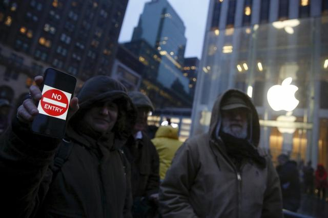 A demonstrator holds a sign during a protest against the FBI's request to extract data from iPhones in cases across the country, outside the Apple Store in New York February 23, 2016. REUTERS/Shannon Stapleton