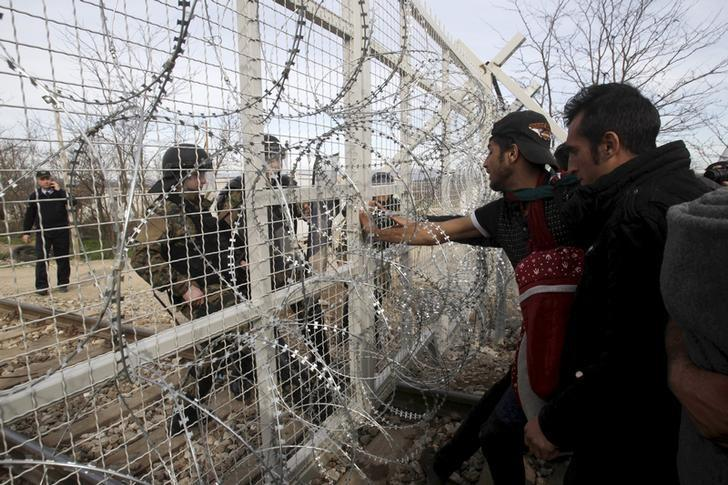 Refugees and migrants stand next to a border fence at the Greek-Macedonian border, after Macedonia closed its borders with Greece for Afghan migrants and demands additional identification from people seeking to cross the border and head to Western Europe, near the village of Idomeni, Greece, February 22, 2016. REUTERS/Alexandros Avramidis