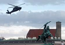 "An Austrian army Sikorsky S-70 ""Black Hawk"" helicopter hovers over a statue of Archduke Charles as it lands in Vienna October 20, 2014. REUTERS/Heinz-Peter Bader"