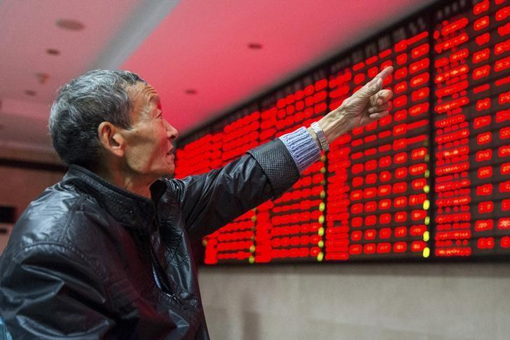 An investor points to an electronic board showing stock information as he speaks to another investor, at a brokerage house in Nanjing, Jiangsu province, China, November 19, 2015. REUTERS/China Daily