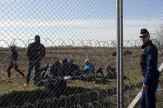 Мигранты отдыхают под присмотром полицейского за колючей проволокой на границе Венгрии с Сербией в районе венгерского Морахалома 22 февраля 2016 года. Планы Венгрии провести референдум, чтобы выразить отношение к обязательным квотам на распределение мигрантов между странами Евросоюза может идти вразрез с согласованной стратегией разрешения миграционного кризиса, заявила Еврокомииссия в четверг. REUTERS/Laszlo Balogh