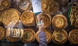 """Покупатель передает деньги продавцу лепешек на Зеленом базаре в Алма-Ате 23 января 2015 года. McDonald""""s Corp в партнёрстве с родственником президента Казахстана назначил на март открытие первого ресторана всемирно известной сети фастфуда - проект, в который владелец франшизы вложил $3,5 миллиона. REUTERS/Shamil Zhumatov"""