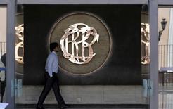 Imagen de archivo de una persona caminando frente al logo del Banco Central de Perú en Lima, Abril 7, 2015.  El Banco Central de Perú informó el domingo que decidió elevar la tasa de encaje bancario en moneda local a un 1 por ciento desde un 0,75 por ciento a partir de marzo, para asegurar un nivel adecuado de liquidez en el mercado interbancario de préstamos.REUTERS/Mariana Bazo