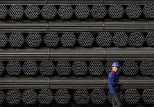 Foto de archivo de un trabajador caminando cerca de una pila de productos de acero, en la planta de Youfa en Tangshan, China. 3 de noviembre de 2015. China dijo el lunes que planea despedir a 1,8 millones de trabajadores en las industrias del carbón y del acero, o alrededor del 15 por ciento de la fuerza de trabajo, como parte de los esfuerzos para reducir el exceso de su capacidad industrial, pero no estableció un plazo. REUTERS/Kim Kyung-Hoon/Files