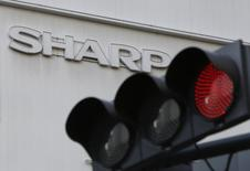 A logo of Sharp Corp is seen behind a traffic signal of red outside an electronics retail store in Tokyo, Japan, February 26, 2016.  REUTERS/Yuya Shino