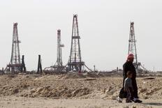 Жители Ирака у нефтяного месторождения Румайла в Басре. 26 января 2016 года. Добыча нефти в ОПЕК в феврале снизилась с рекордного уровня за счет остановки поставок с севера Ирака и перебоев в других странах, показал опрос Рейтер. REUTERS/Essam Al-Sudani