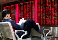 Un inversor lee un diario frente a un tablero electrónico que muestra información bursátil, en una correduría en Pekín, China, 16 de febrero de 2016. Las acciones chinas subieron el martes después de que el banco central recortó los requerimientos de reservas para los prestamistas el lunes, lo que llevó a los inversores a hacer caso omiso a unos sondeos decepcionantes de manufactura y servicios. REUTERS/Kim Kyung-Hoon