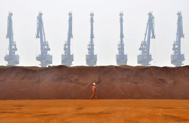 A worker walks past a pile of iron ore from Australia at a port in Tianjin municipality in this March 29, 2010 file photo. REUTERS/Vincent Du/Files