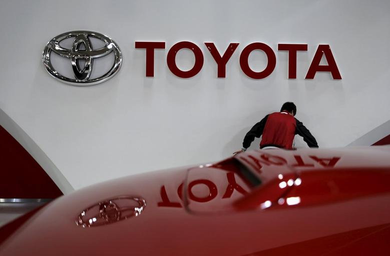 An employee works under a Toyota Motor Corp logo at the company's showroom in Tokyo, Japan February 5, 2016. REUTERS/Toru Hanai