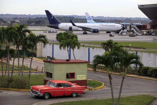 Blue Panorama and KLM aircrafts are seen as a taxi drives out of a parking lot at Havana's Jose Marti International Airport February 15, 2016.  REUTERS/Enrique de la Osa