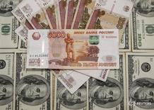 Рублевые и долларовые купюры в Сараево 9 марта 2015 года. Рубль начал снижением торги четверга на фоне текущей негативной динамики нефти после тестирования многонедельных максимумов. REUTERS/Dado Ruvic