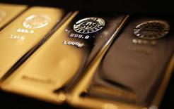 Слитки золота в магазине  Ginza Tanaka в Токио 18 апреля 2013 года. Цены на золото растут за счет поступления средств в ETF-фонды и надежды инвесторов на продолжение роста котировок в этом году, несмотря на возобновление спроса на рискованные активы. REUTERS/Yuya Shino