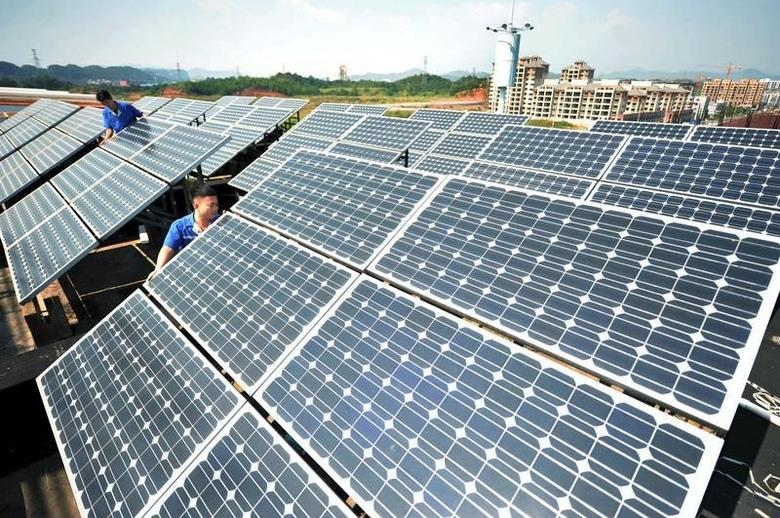 Workers install solar panels on the rooftop of a company in Shangrao, Jiangxi province, China, October 11, 2015.  REUTERS/Stringer