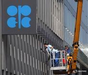 Рабочие моют окна в штаб-квартире ОПЕК в Вене 7 апреля 2014 года. Представители нескольких стран из организации нефтеэкспортёров (ОПЕК) и стран, не входящих в картель, планируют встречу в России приблизительно 20 марта, сказал на конференции министр нефти Нигерии Эммануэль Качикву. REUTERS/Heinz-Peter Bader
