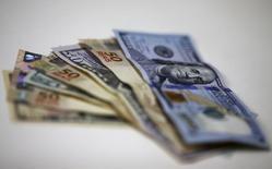 Billetes de real y dólar en una casa de cambio en Río de Janeiro. 10 de septiembre de 2015. Las monedas latinoamericanas continuarán volátiles después de una recuperación inesperada el mes pasado, pues la crisis política de Brasil seguiría perjudicando al real y el panorama del peso mexicano estará nublado por las señales de deterioro económico, mostró el jueves un sondeo de Reuters. REUTERS/Ricardo Moraes