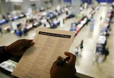 """A person looks over his choices of firms that are interviewing at a U.S. Chamber of Commerce Foundation """"Hiring Our Heroes"""" military job fair in Washington January 8, 2016.  REUTERS/Gary Cameron"""