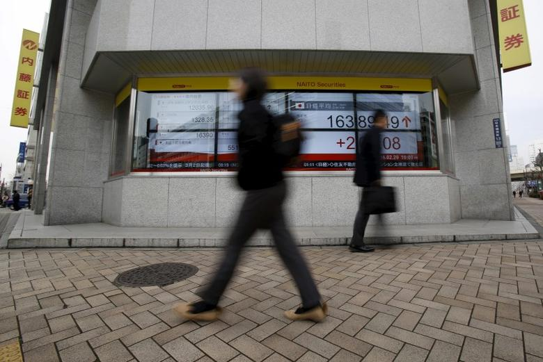 Pedestrians walk pass an electronic board showing the Japan's Nikkei average (R) and other stock market indices outside a brokerage in Tokyo, Japan, February 29, 2016. REUTERS/Yuya Shino
