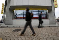 Peatones caminan junto a un tablero electrónico que muestra el índice Nikkei, afuera de una correduría en Tokio, Japón, 29 de febrero de 2016. Las acciones japonesas subieron el viernes en una sesión volátil, pero las ganancias fueron limitadas en momentos en que los inversores aguardan con cautela un reporte clave de empleo en Estados Unidos. REUTERS/Yuya Shino