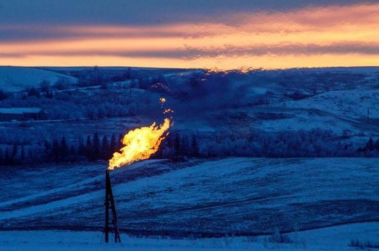 A natural gas flare on an oil well pad burns as the sun sets outside Watford City, North Dakota January 21, 2016. REUTERS/Andrew Cullen
