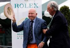 Tennis Hall of Fame member Bud Collins (L) is helped up by fellow Tennis Hall of Famer Owen Davidson as he greets the crowd gathered for the Tennis Hall of Fame Induction Ceremony in Newport, Rhode Island in this file July 13, 2013 photo. REUTERS/Jessica Rinaldi
