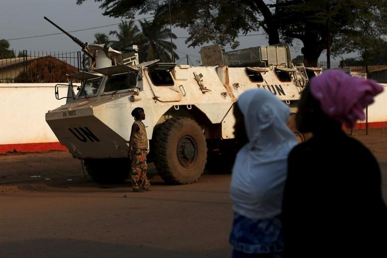 Women walk by a United Nations peacekeeping armoured vehicle guarding the outer perimeter of a compound of a school used as an electoral centre at the end of the presidential and legislative elections, in the mostly muslim PK5 neighbourhood of Bangui, Central African Republic, February 14, 2016. REUTERS/Siegfried Modola