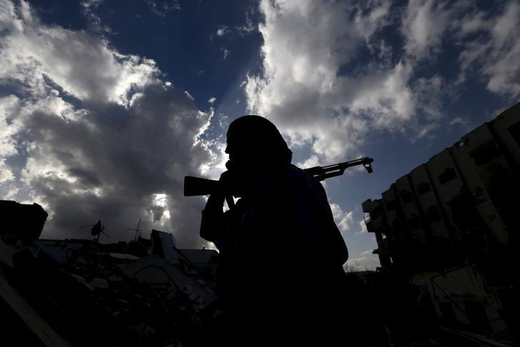 A rebel fighter carries his weapon in the rebel-controlled area of Jobar, a suburb of Damascus, Syria March 3, 2016. REUTERS/Bassam Khabieh