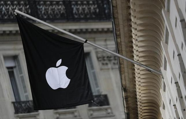 An Apple logo is seen on a flag on the facade of the Apple Store in Paris, March 3, 2016. REUTERS/Christian Hartmann