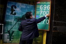 Imagen de archivo de un trabajador ordenando una pizarra con cotizaciones entre el peso chileno y otras monedas en una casa de cambios en Santiago, ago 20, 2015. Las monedas latinoamericanas recortaron las fuertes pérdidas que sufrieron en el arranque del año gracias a un repunte de todos los activos de riesgo liderado por la mejora de las acciones en Wall Street, acercándose a un techo de sus rangos de cotización del que podrían bajar fácilmente en un ambiente muy volátil.    REUTERS/Ivan Alvarado