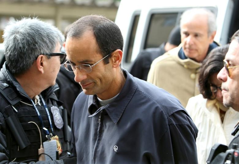 Marcelo Odebrecht (2nd L), the head of Latin America's largest engineering and construction company Odebrecht SA, and Otavio Marques Azevedo (R, background), CEO of Andrade Gutierrez, are escorted by Federal Police as they arrived at the Institute of Forensic Science in Curitiba, Brazil, June 20, 2015.  REUTERS/Rodolfo Burher