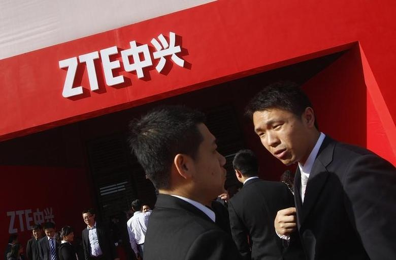 Guests and employees chat under a ZTE company logo in front of the venue of the company's 15th anniversary celebration in Beijing April 18, 2013. REUTERS/Barry Huang