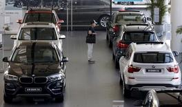 A man takes a look at BMW cars at a dealer shop in Beijing, China, September 11, 2015. REUTERS/Kim Kyung-Hoon