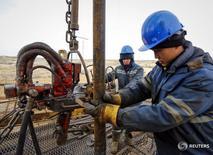 Рабочие проверяют оборудование на нефтяном месторождении РД Казмунайгаз в Кызылординской области Казахстана 21 января 2016 года. Казахстан может повысить план добычи нефти на 2016 год при достижении средней цены до $40 за баррель на мировых рынках до 77 миллионов тонн с запланированных 74 миллионов, сказал журналистам министр энергетики Владимир Школьник. REUTERS/Shamil Zhumatov
