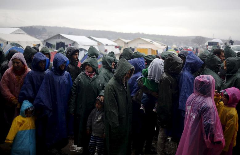 Migrants line up for food during a heavy rainfall at a makeshift camp on the Greek-Macedonian border, near the village of Idomeni, Greece March 9, 2016.  REUTERS/Stoyan Nenov