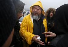 Chinese dissident artist Ai Weiwei speaks to migrants as he visits a makeshift camp on the Greek-Macedonian border, near the village of Idomeni, Greece, March 9, 2016. Ai is in Greece to shoot a documentary. REUTERS/Stoyan Nenov